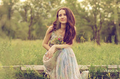 Pretty girl sitting in the meadow. Beautiful girl sits with a bouquet of flowers on a meadow stock photo