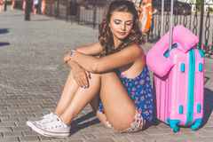Pretty girl is sitting near suitcase Stock Photography