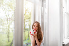 Pretty girl sitting near the window and looking at the camera wi Royalty Free Stock Images