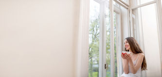 Pretty girl sitting near the window and looking out the window w Royalty Free Stock Photos