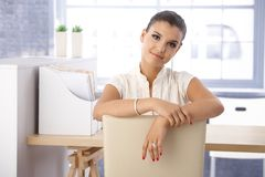 Pretty girl sitting in office Stock Photography
