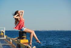 Pretty girl sitting at the old berth Stock Photos