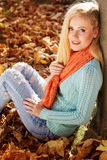 Pretty girl is sitting in park on yellow maple Stock Image