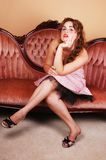 Pretty girl sitting on pink sofa. Stock Image