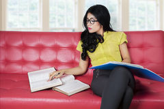 Pretty girl sitting on red sofa while reading books Stock Images