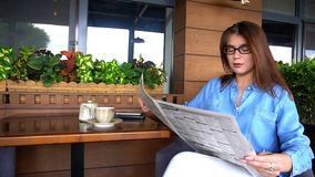 Pretty girl sitting at restaurant arm chair and reading newspape. Beautiful woman resting and reading newspaper articles at restaurant in . Charming female Royalty Free Stock Image