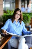 Pretty girl sitting at restaurant arm chair and reading newspape. Beautiful woman resting and reading newspaper articles at restaurant  . Charming female person Royalty Free Stock Image