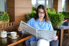 Pretty girl sitting at restaurant arm chair and reading newspape. Beautiful woman resting and reading newspaper articles at restaurant  . Charming female person Stock Photos