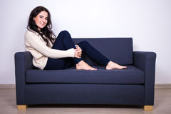 Pretty girl sitting on sofa at home Stock Photos