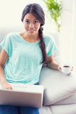 Pretty girl sitting on a sofa using laptop smiling at camera Stock Photo