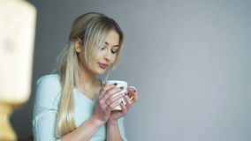 Pretty girl sitting on the stairs and drinking a coffee in 4K stock footage
