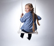 Pretty girl sitting on swing Royalty Free Stock Image