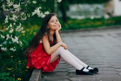 Pretty girl sitting under the cherry tree Stock Photos