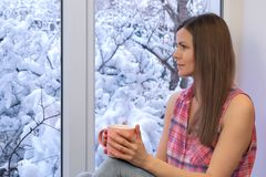 Pretty girl sitting on the windowsill, looking the window and drinking tea. Winter outside. Pretty girl sitting on the windowsill, looking the window and Royalty Free Stock Image