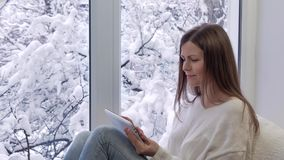 Pretty girl sitting on the windowsill, looking the window and using tablet computer. Winter outside. Pretty girl sitting on the windowsill, looking the window stock footage