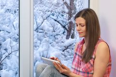 Pretty girl sitting on the windowsill, looking the window and using tablet computer. Winter outside. Pretty girl sitting on the windowsill, looking the window Royalty Free Stock Photography