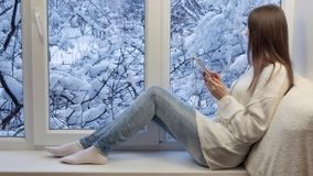 Pretty girl sitting on the windowsill and using tablet computer with earphones. Winter outside. Pretty girl sitting on the windowsill and using tablet computer stock footage
