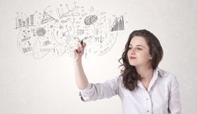Pretty girl sketching graphs and diagrams on wall Royalty Free Stock Photo