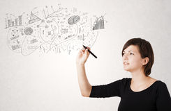 Pretty girl sketching graphs and diagrams on wall Stock Image