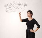 Pretty girl sketching graphs and diagrams on wall Stock Photos
