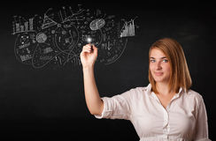 Pretty girl sketching graphs and diagrams on wall Stock Photo