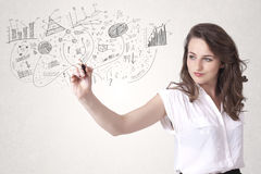 Pretty girl sketching graphs and diagrams on wall. Pretty girl sketching graphs and diagrams on white wall stock photos