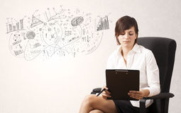 Pretty girl sketching graphs and diagrams on wall Royalty Free Stock Photos