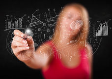 Pretty girl sketching graphs and diagrams on wall. Pretty girl sketching graphs and diagrams on white wall Royalty Free Stock Image