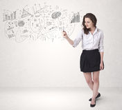 Pretty girl sketching graphs and diagrams on wall Stock Images