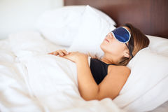Pretty girl with a sleep mask. Profile view of a young woman wearing a sleep mask in a comfortable bed at a hotel royalty free stock photos