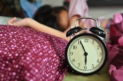Pretty girl sleeping on the background of a retro alarm clock stock photo