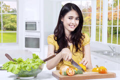 Pretty girl slicing vegetables in the kitchen Royalty Free Stock Photography