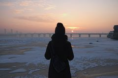 Pretty girl with a small backpack on her back is enjoying magical sunrise on the banks of the Dnieper River in Kyiv, Ukraine. Cold winter morning Royalty Free Stock Photo
