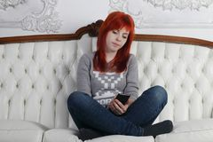Pretty girl with smartphone squats crosslegged. On white sofa in white room Royalty Free Stock Photography