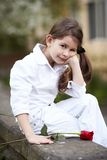 Pretty girl smell rose outdoor in white suit Royalty Free Stock Photo