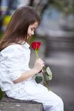 Pretty girl smell rose outdoor in white suit Royalty Free Stock Photos