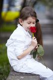 Pretty girl smell rose outdoor in white suit Royalty Free Stock Images