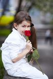 Pretty girl smell rose outdoor in white suit Royalty Free Stock Photography