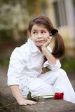 Pretty girl smell rose outdoor in white suit Stock Photo