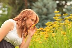 Pretty girl smelling a flower Stock Images