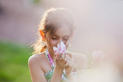 Pretty girl smells at blossom Stock Images