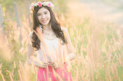 Pretty girl smiles in spring flower grass field Stock Photography