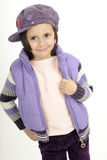 Pretty girl smiling. Young fashion model posing with purple cap and jacket Royalty Free Stock Photography