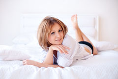 Pretty girl smiling in bed in the morning Stock Images