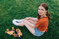 Pretty girl smiling at camera while sitting on grass with vintage. Roller skates royalty free stock photos