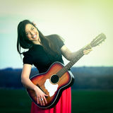 Pretty girl smiling with a guitar royalty free stock images