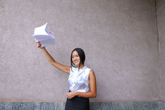 Pretty girl smiling, posing, holds in hands and scatters paper a Stock Images