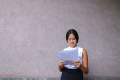 Pretty girl smiling, posing, holds paper in hands and looking aw Stock Images
