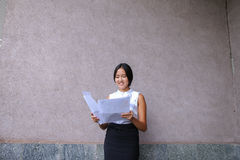 Pretty girl smiling, posing, holds paper in hands and looking aw Stock Photography