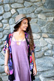 Pretty girl smiling at something off to the side. A cute teenager, standing near a rock wall. She is wearing a purple dress, floral kimono and a hat. She is Stock Images
